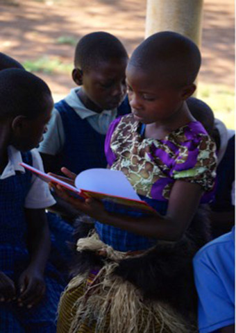 Joanne, one of the pupils at NCLC reading Tales of Nabugabo